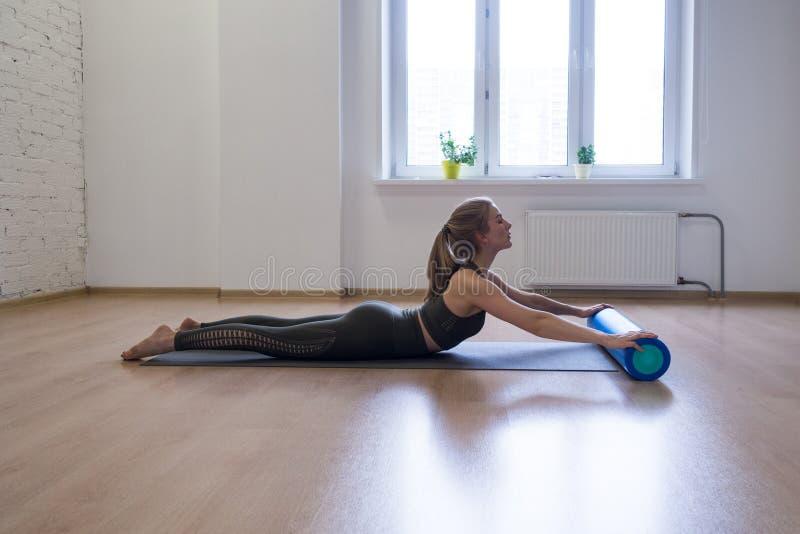 Esercizio d'allungamento posteriore con il rullo della schiuma La giovane donna alza il suo corpo superiore, fa i pilates nello s fotografia stock libera da diritti