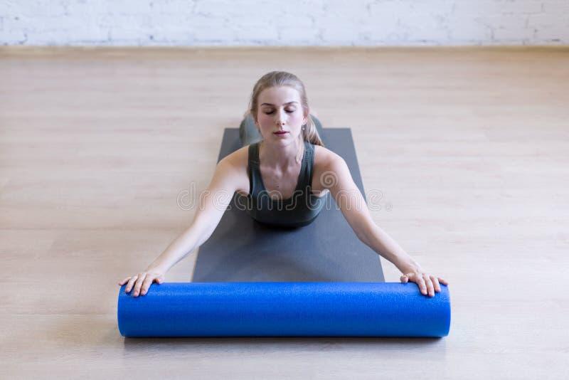 Esercizio d'allungamento posteriore con il rullo della schiuma La giovane donna alza il suo corpo superiore, fa i pilates nello s immagine stock