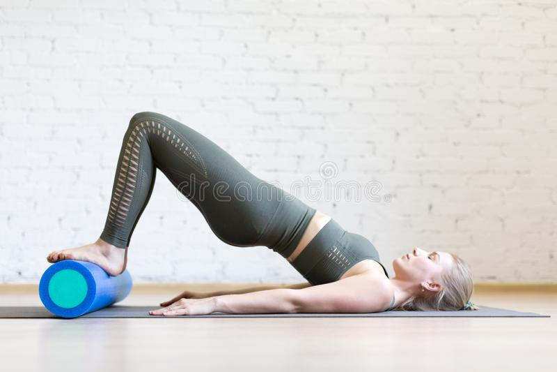 esercizio del Mezzo ponte con il rullo della schiuma La giovane donna fa i pilates nello studio del sottotetto immagine stock libera da diritti