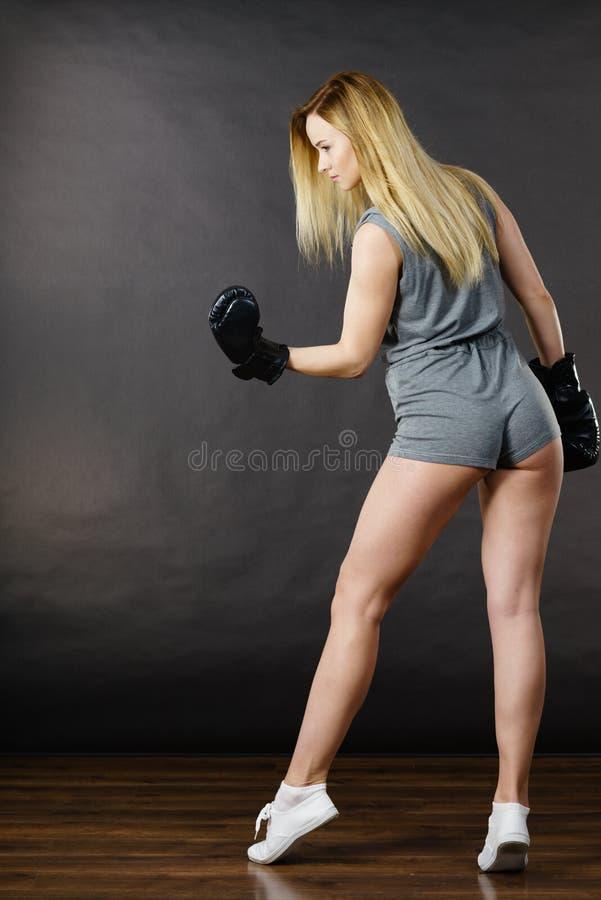 Esercizio della ragazza del pugile con i guantoni da pugile fotografie stock libere da diritti