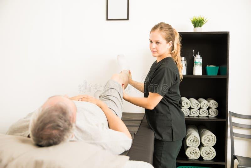 Esercizio di gamba di Helping Patient With del terapista fisico per dolore con riferimento a immagini stock libere da diritti