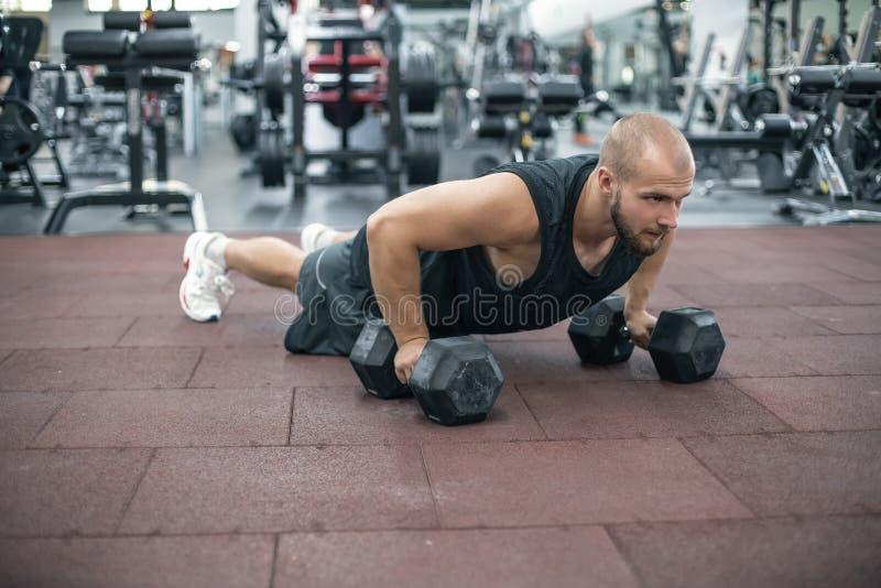Esercizio di piegamento sulle braccia di forza di flessione dell'uomo della palestra con la testa di legno in un allenamento di f fotografie stock