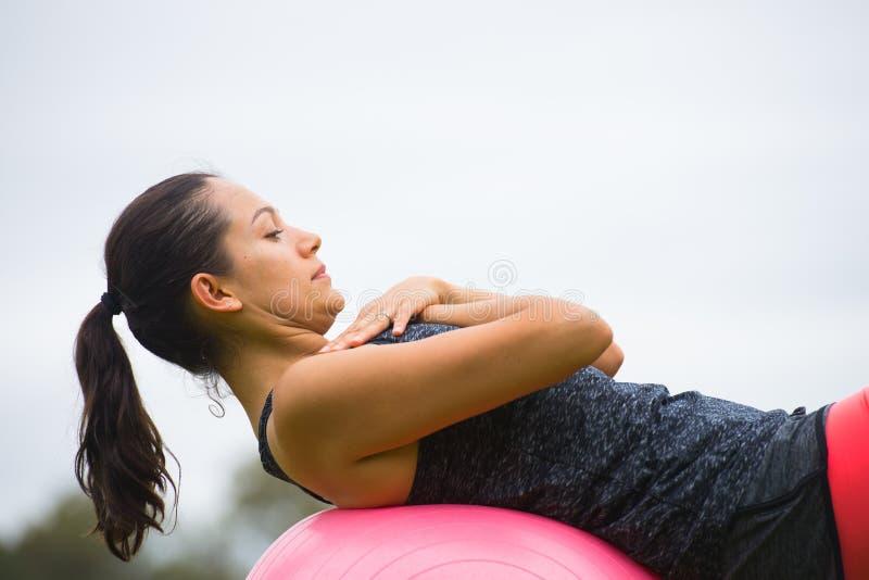 Esercizio di yoga della giovane donna sulla palla di misura fotografia stock libera da diritti