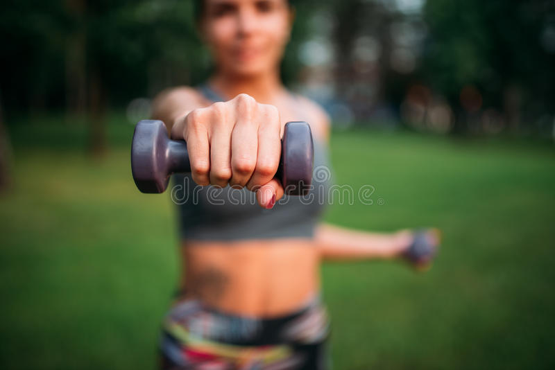 Esercizio sportivo della ragazza con le teste di legno in parco fotografia stock libera da diritti