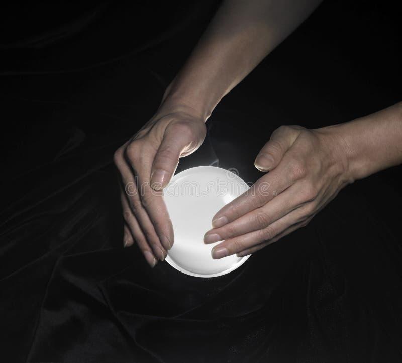 Esfera de cristal e mãos ao redor foto de stock royalty free
