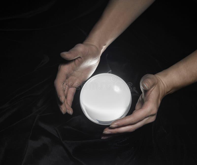 Esfera de cristal e mãos ao redor fotos de stock royalty free