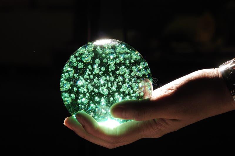 Esfera de cristal verde na mão imagem de stock