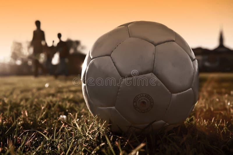 Esfera de futebol com a silhueta dos povos na prata foto de stock