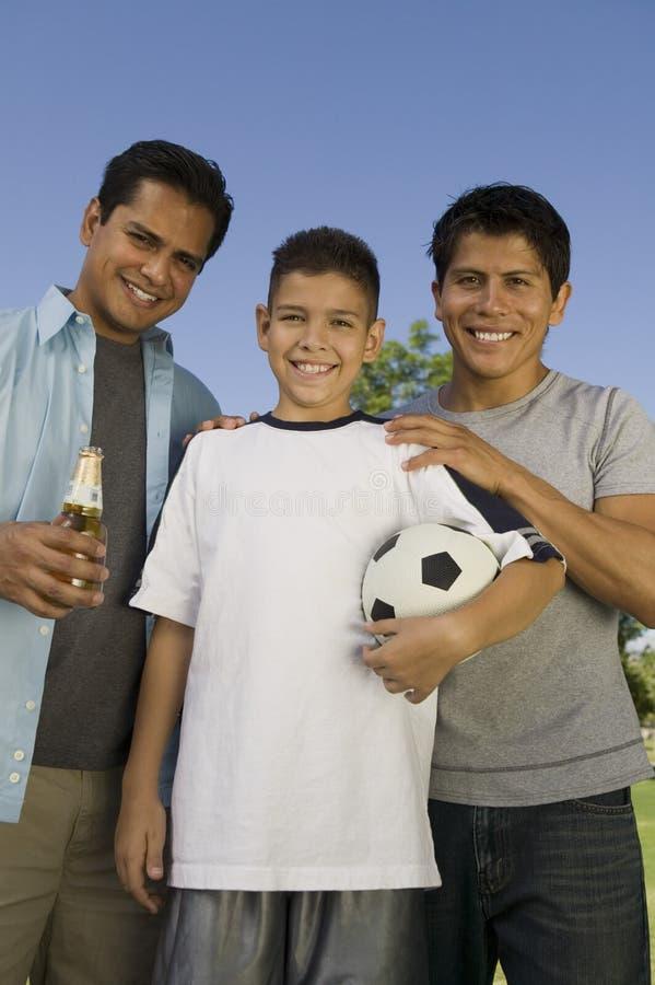 Esfera de futebol da terra arrendada do menino imagem de stock