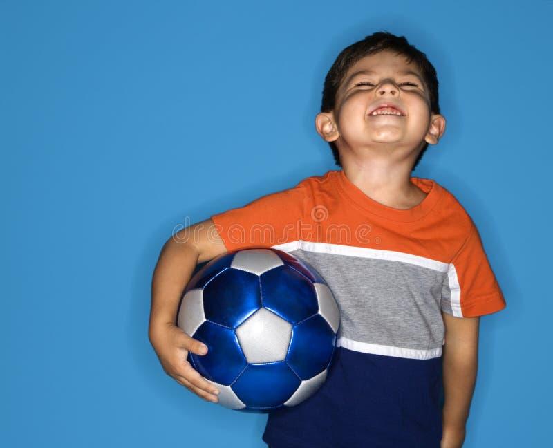 Esfera de futebol da terra arrendada do menino. fotos de stock