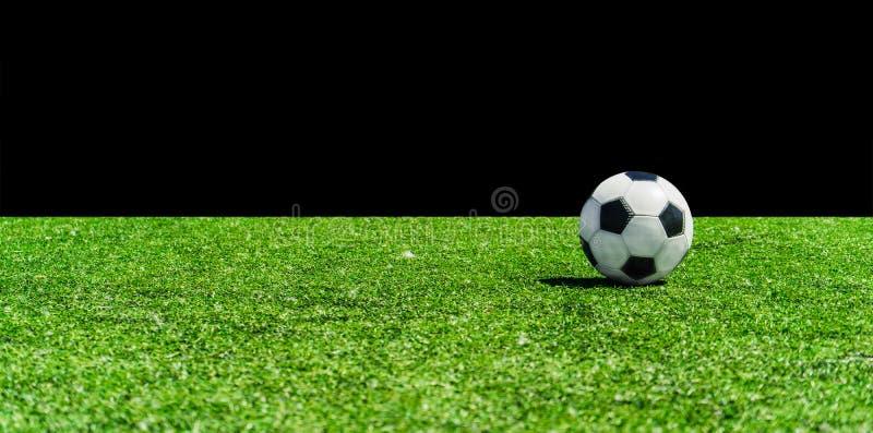 Esfera de futebol na grama de encontro ao fundo preto foto de stock