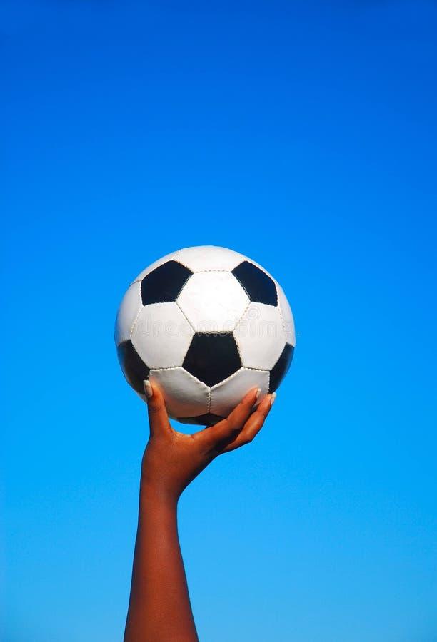 Esfera de futebol na mão preta foto de stock