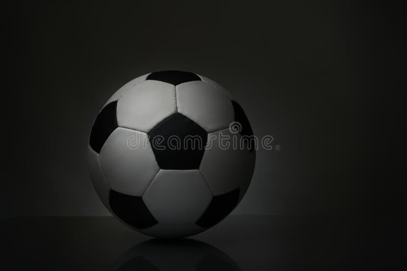 Esfera de futebol no fundo escuro ilustração do vetor