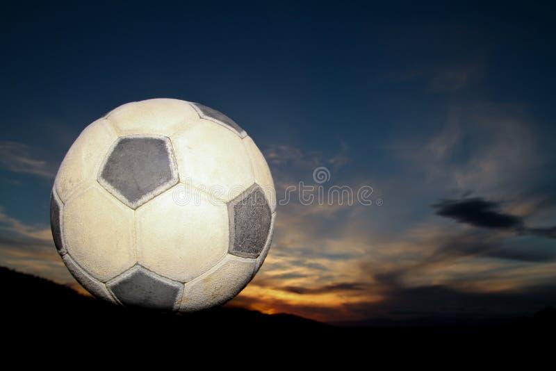 Esfera de futebol no por do sol fotografia de stock royalty free