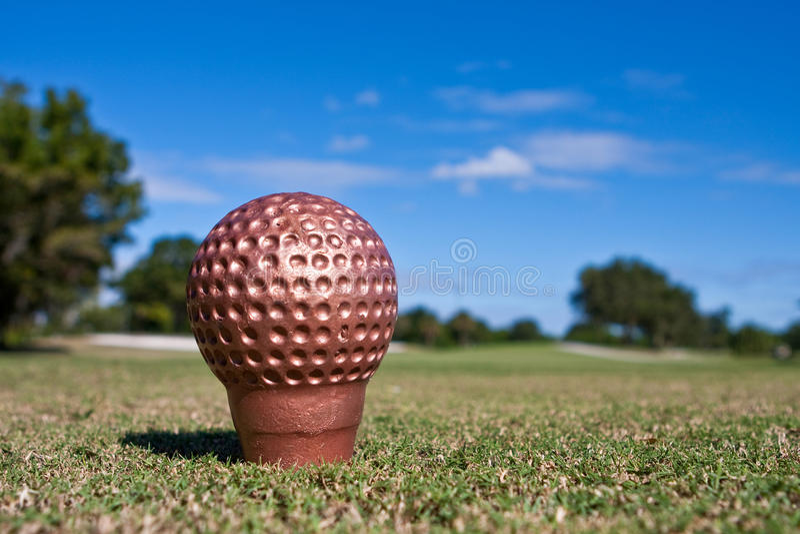 A esfera de golfe dourada imagem de stock