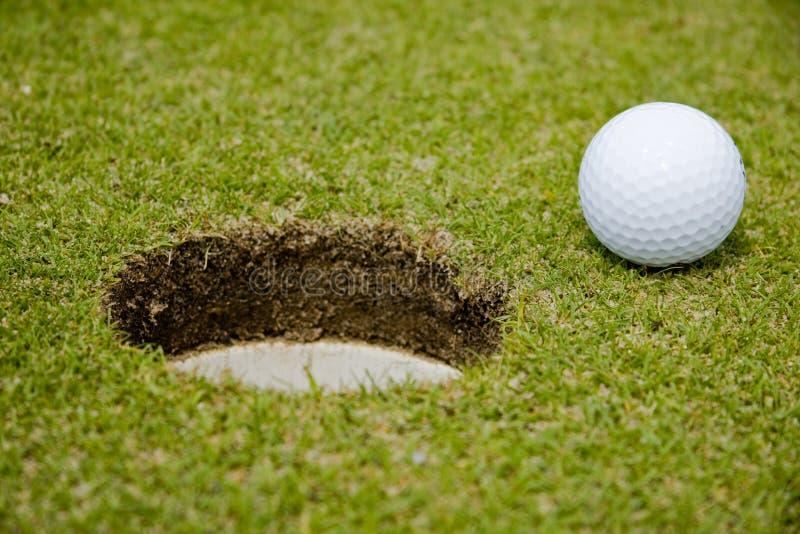 Esfera de golfe muito perto a um furo fotos de stock royalty free
