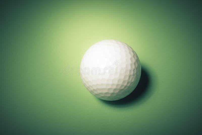 Esfera de golfe no fundo verde fotografia de stock
