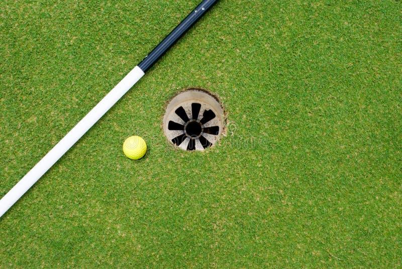 Esfera de golfe no furo imagem de stock royalty free