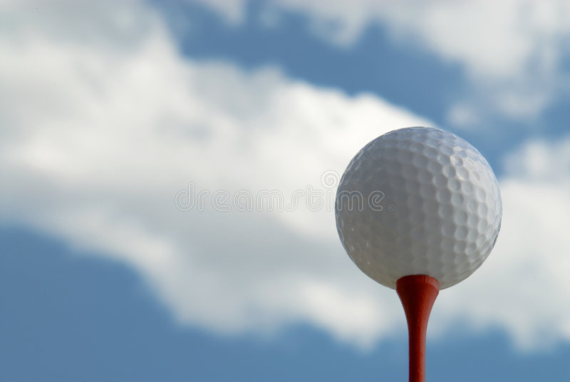 Esfera de golfe no T de encontro ao céu nebuloso foto de stock