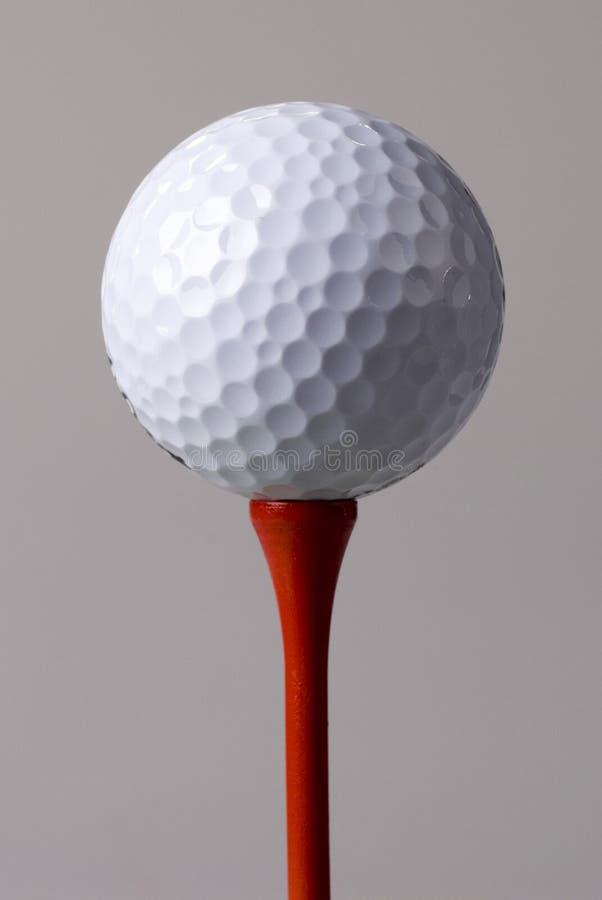 Esfera de golfe no T vermelho foto de stock