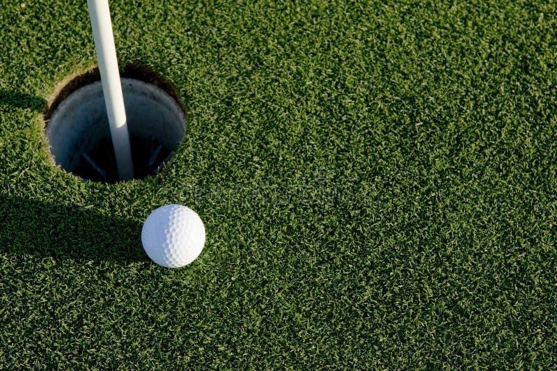 Esfera de golfe perto do furo fotos de stock royalty free
