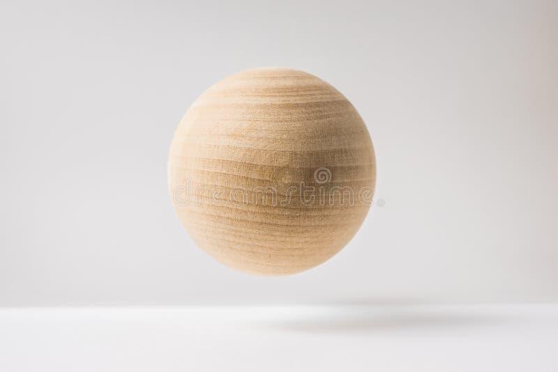 Esfera de madera real abstracta con la disposición surrealista en el fondo superficial blanco fotografía de archivo