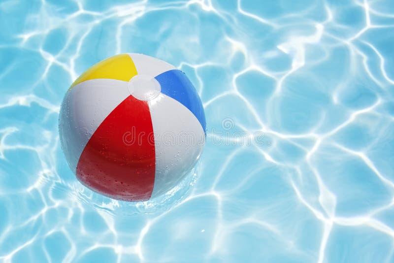Esfera de praia na piscina fotografia de stock