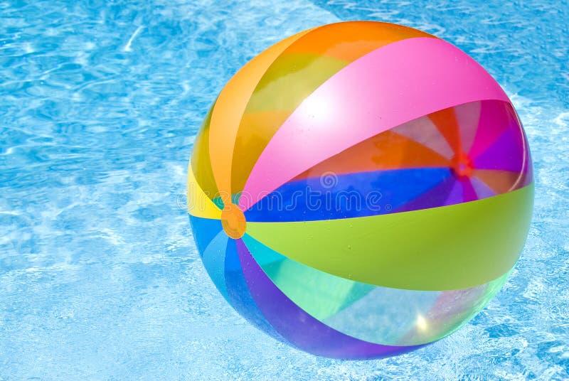 Esfera de praia na piscina fotografia de stock royalty free