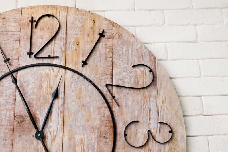 Esfera de reloj de madera en la pared blanca foto de archivo
