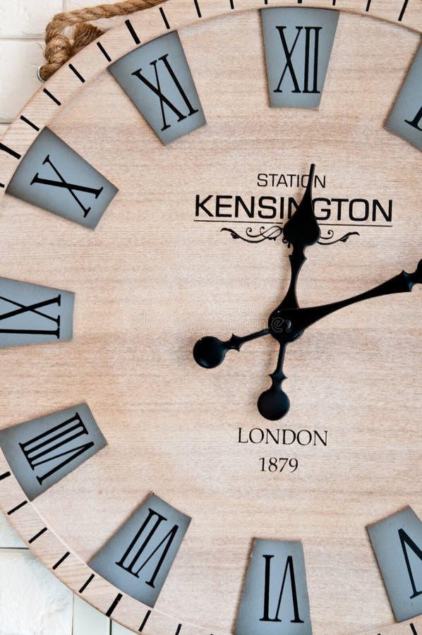Esfera de reloj de madera en la pared blanca imagen de archivo
