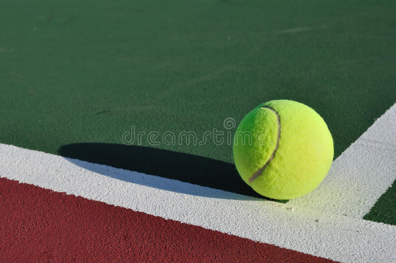 Esfera de tênis amarela na corte fotografia de stock royalty free