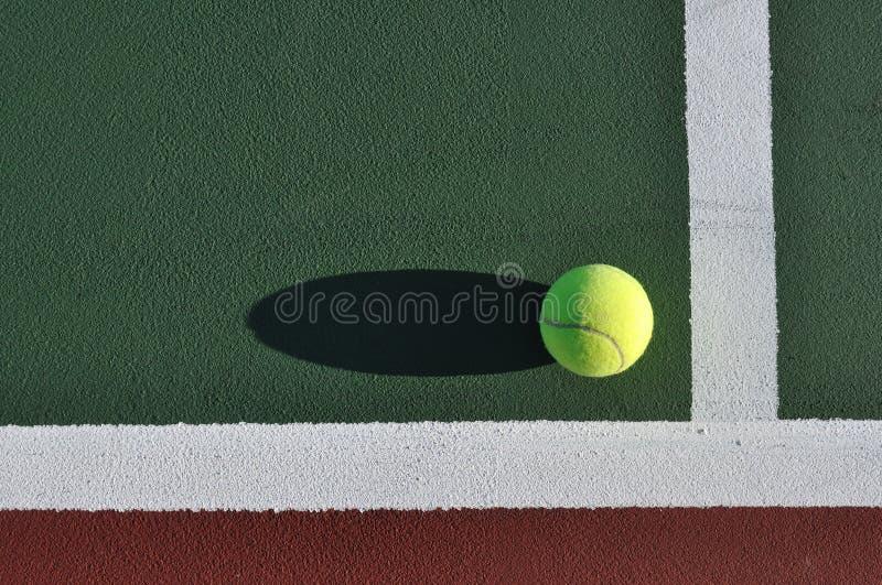 Esfera de tênis amarela na corte imagens de stock