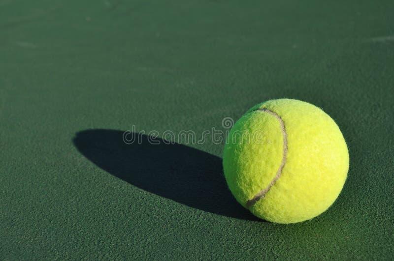 Esfera de tênis amarela na corte fotografia de stock