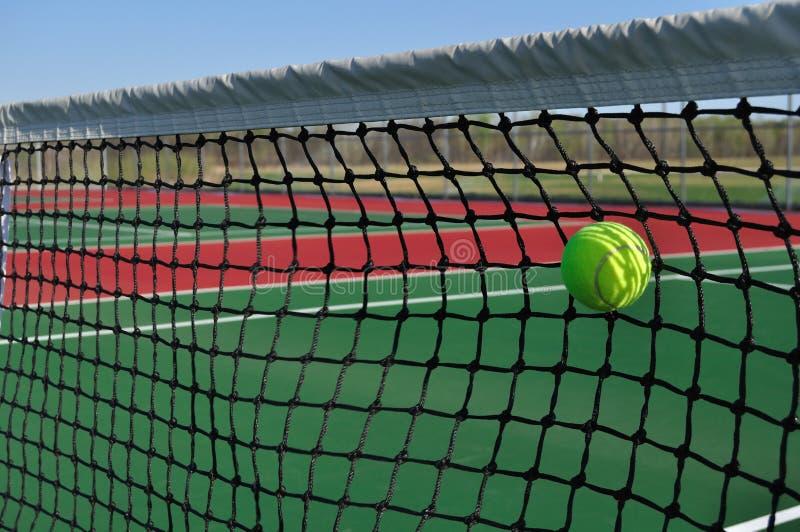 Esfera de tênis amarela que bate a rede imagem de stock