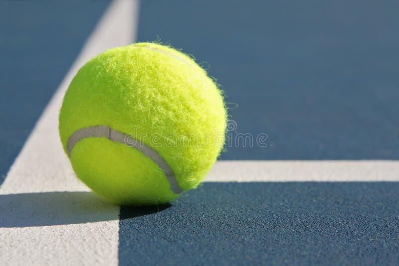 Esfera de tênis na corte azul foto de stock