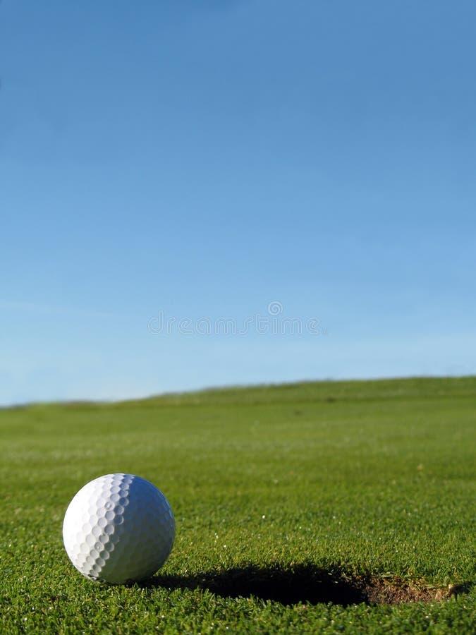 Esfera do campo de golfe ao lado do furo fotografia de stock royalty free