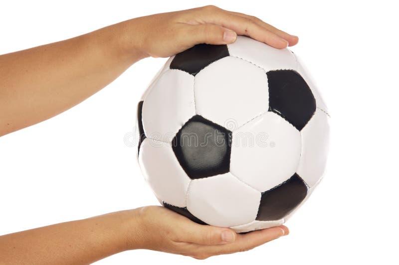 Esfera do futebol nas mãos imagem de stock royalty free