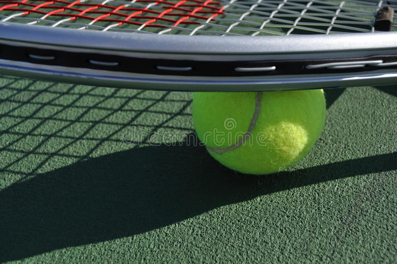 Esfera e raquete amarelas de tênis fotografia de stock royalty free