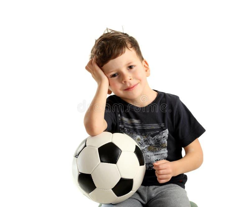 Esfera e recreação de futebol da terra arrendada do menino fotografia de stock royalty free