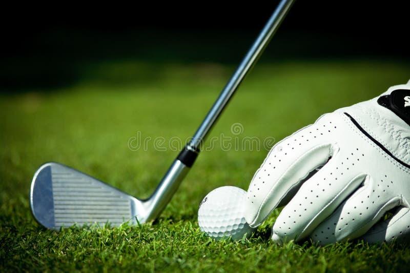 Esfera, ferro e mão de golfe no curso imagens de stock