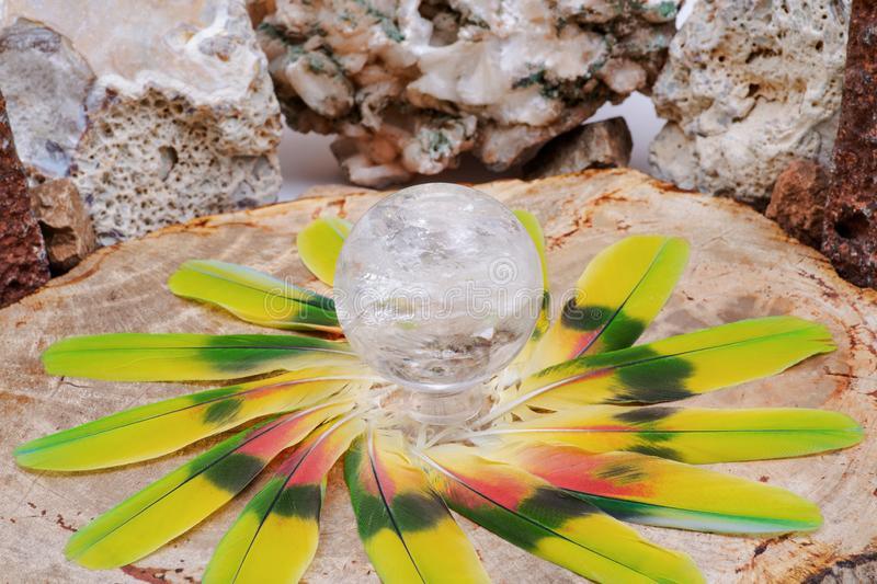 Esfera mágica de cristal da esfera de quartzo do espaço livre de Lemurian no meio de um círculo feito de penas coloridas foto de stock royalty free