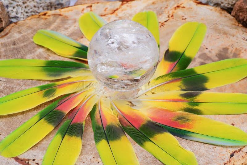 Esfera mágica de cristal da esfera de quartzo do espaço livre de Lemurian no meio de um círculo feito de penas coloridas fotos de stock royalty free