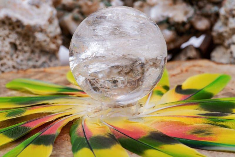Esfera mágica de cristal da esfera de quartzo do espaço livre de Lemurian no meio de um círculo feito de penas coloridas imagens de stock royalty free