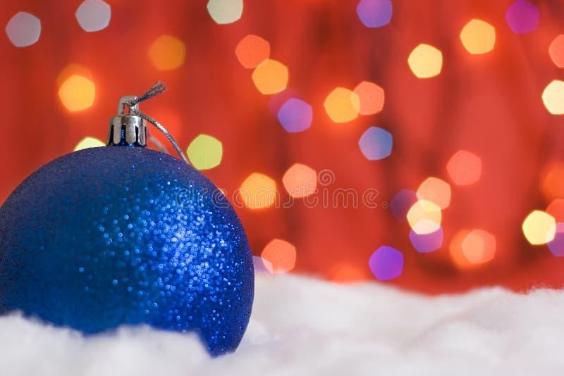 Esferas do Natal na neve e nas luzes fotografia de stock