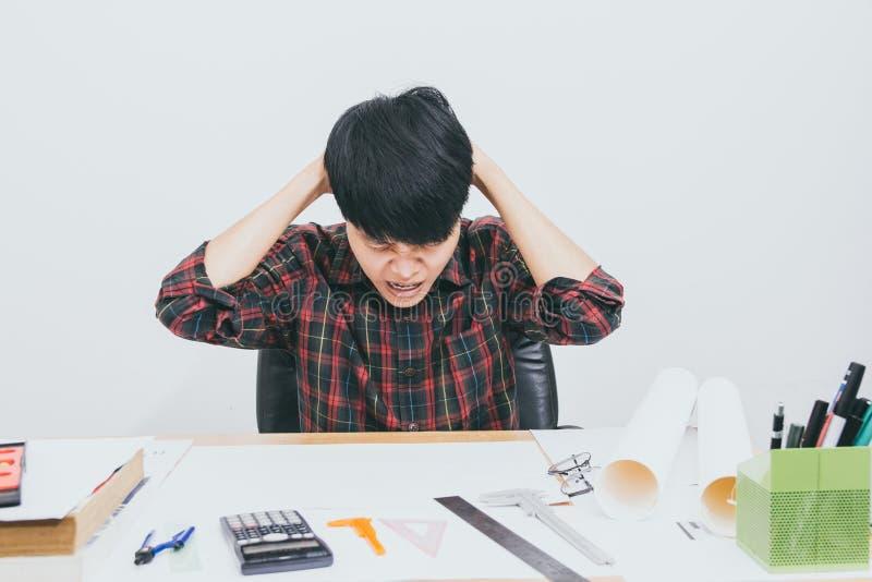 Esforço de assento do homem asiático com trabalho na tabela no escritório da sala imagem de stock