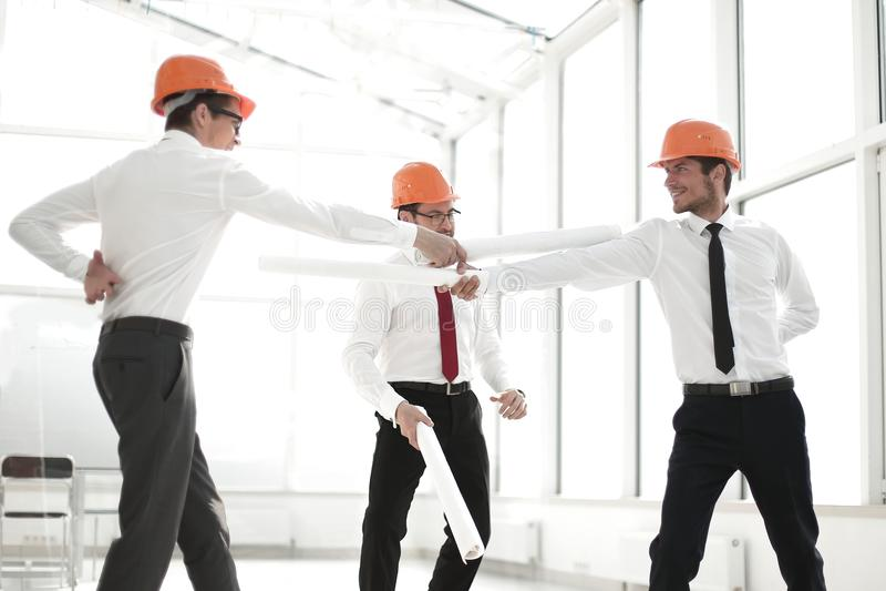 Esforço de três arquitetos com planos reduzidos da construção imagem de stock
