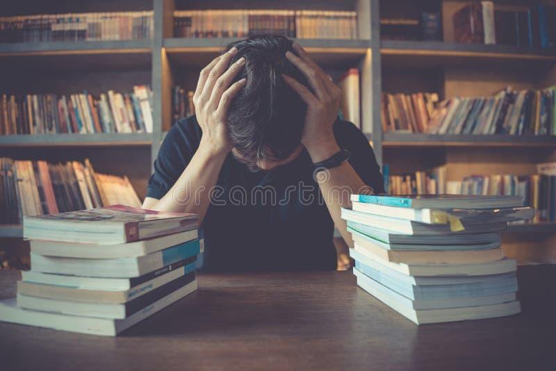 Esforço e homem cansado sob a pressão mental quando livro de leitura que prepara o exame na biblioteca imagem de stock royalty free