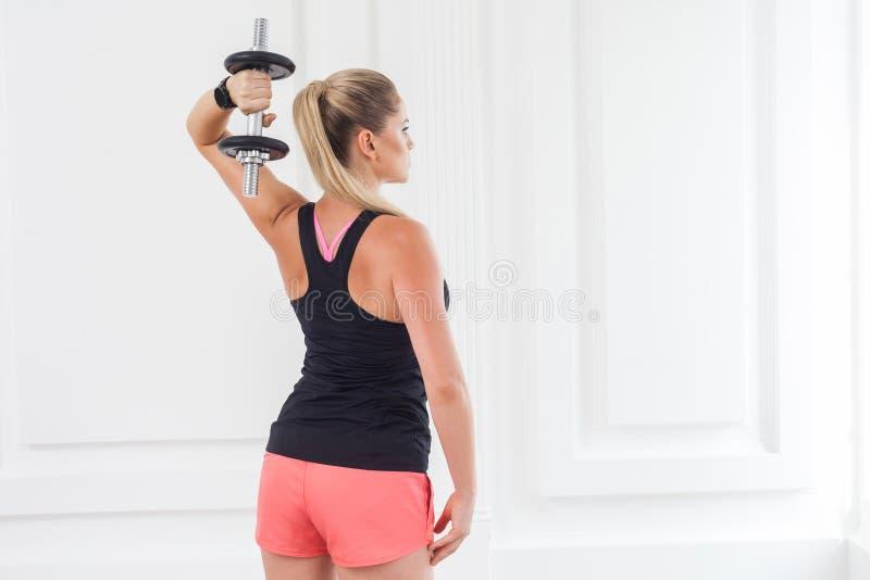 Esfuerzo para fuerte Parte trasera de la mujer atlética del culturista de la motivación adulta joven en pantalones cortos rosados imagen de archivo