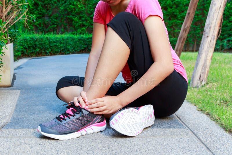 Esguince deportivo asiático del tobillo de la mujer mientras que activa o corre fotografía de archivo libre de regalías