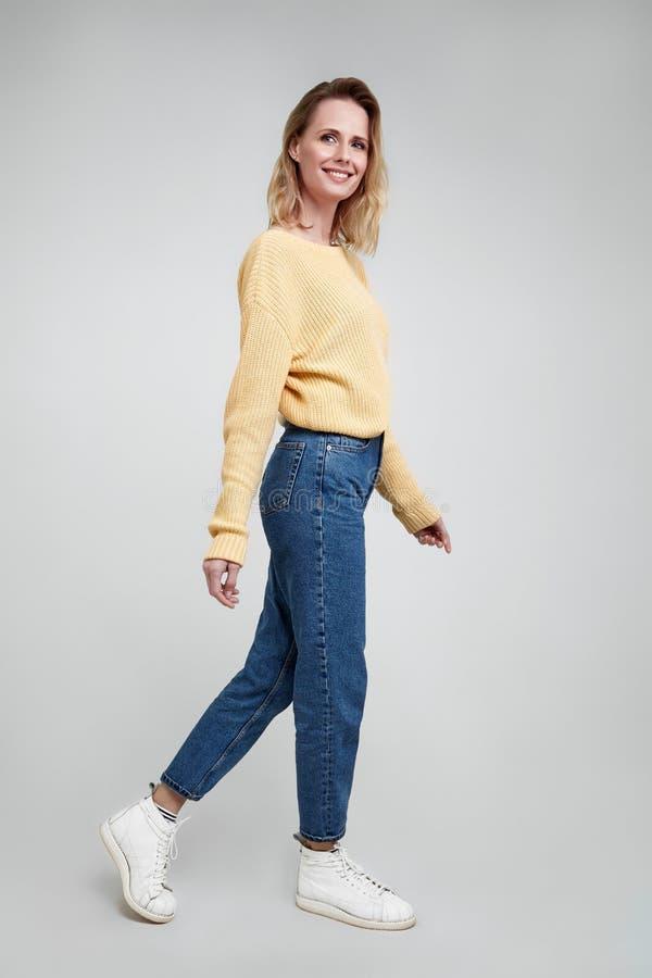 Esile e bello Colpo integrale dello studio della giovane donna attraente nell'abbigliamento casual che tiene mano sull'aria e sul immagine stock